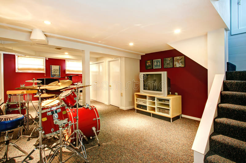 White and red rehearsal basement room. White basement room with red and burgundy walls, carpet floor. Rehearsal room with drums stock photos