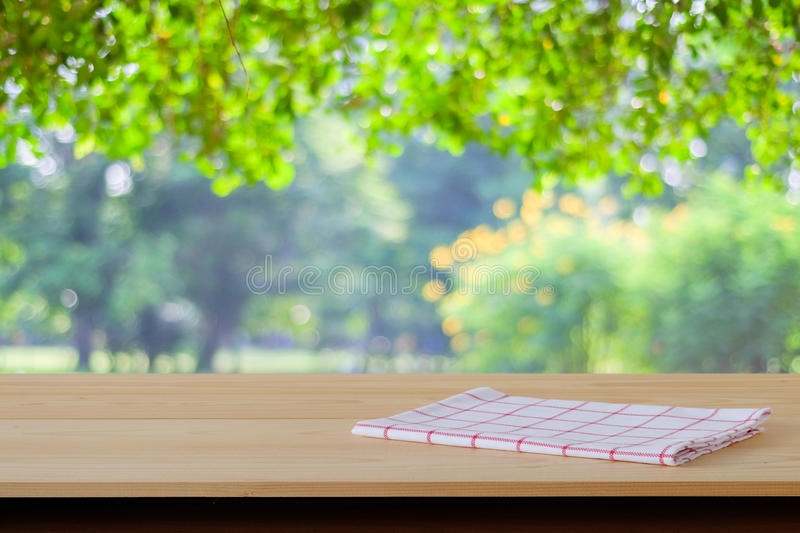 White and red tartan cloth on wood table over blur garden background. Food display montage royalty free stock photo