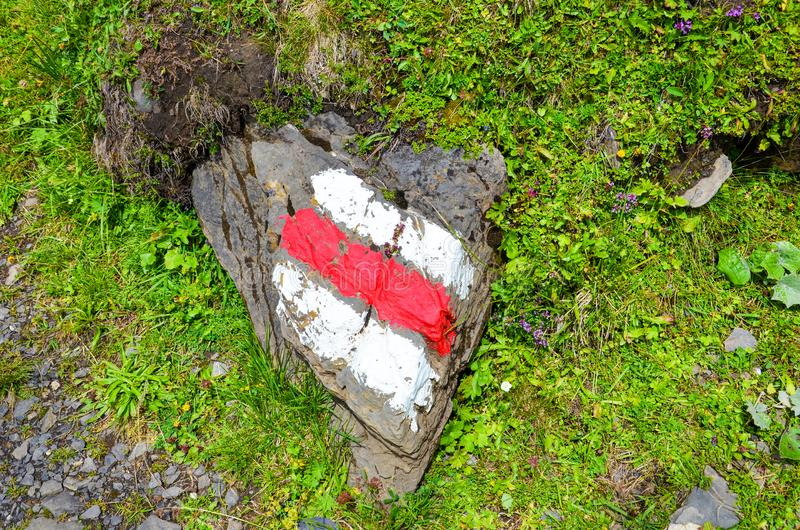White red tourist sign painted on a rock in nature. The marks help for orientation on a hiking trail. Trailblazing, waymarking. Hike, nordic walking. Outdoor stock images