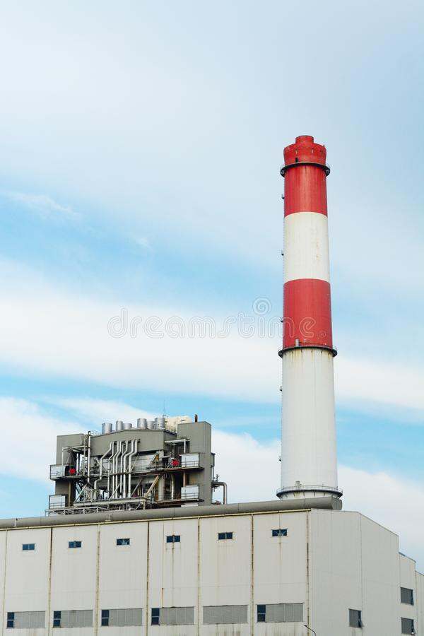 White and red vertical pipe flue-gas stack of power plant with blue sky background. royalty free stock photo