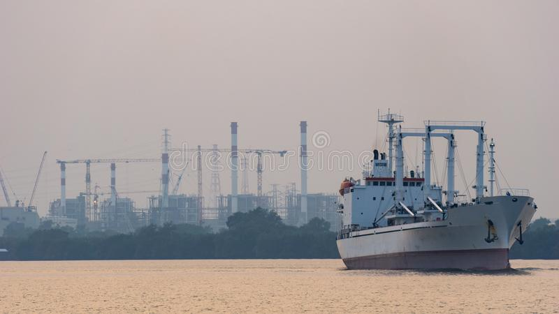 White reefer ship or refrigerated cargo ship sails in Chao Phraya river in the evening. With power plants in the background royalty free stock photography