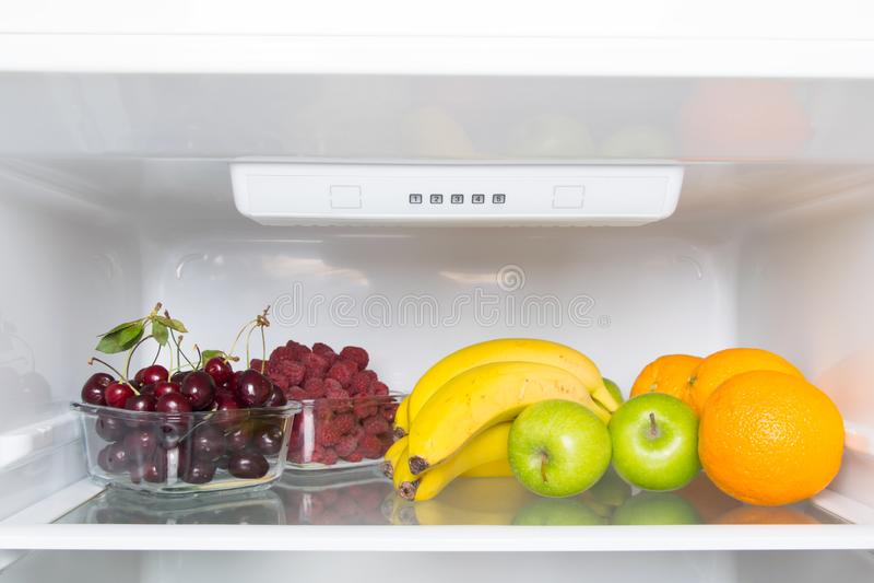 White refrigerator shelf close-up, fruits and berries, raspberries and cherries royalty free stock photo