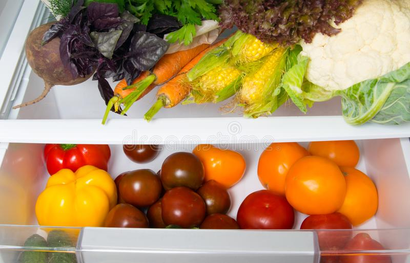 In a white refrigerator on the shelves, close-up of fresh vegetables, tomatoes, peppers, carrots, corn, cucumbers, beets, greens stock image