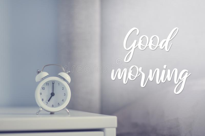 White retro alarm clock in the bedroom. Good morning card.  royalty free stock photo