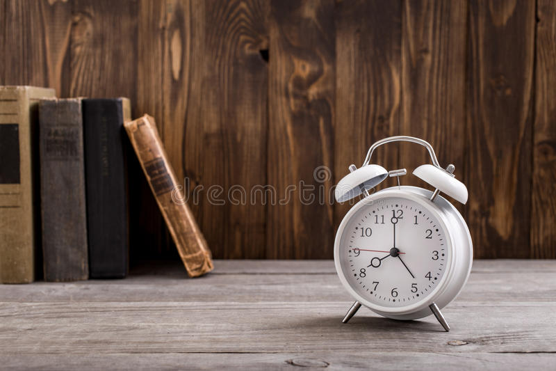 White retro alarm clock with books on wooden table. Close up with copy space stock image