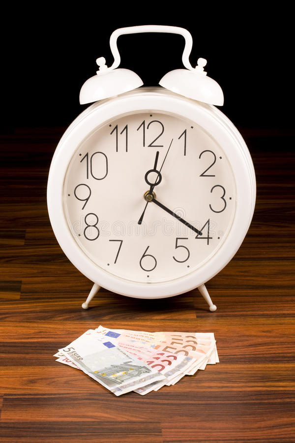 White retro alarm clock and money stock photo