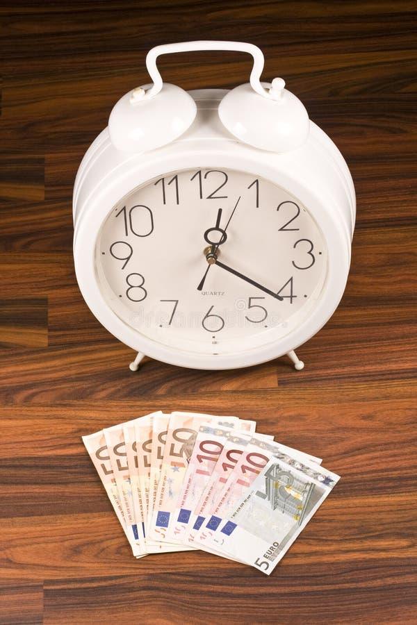 White retro alarm clock and money stock image