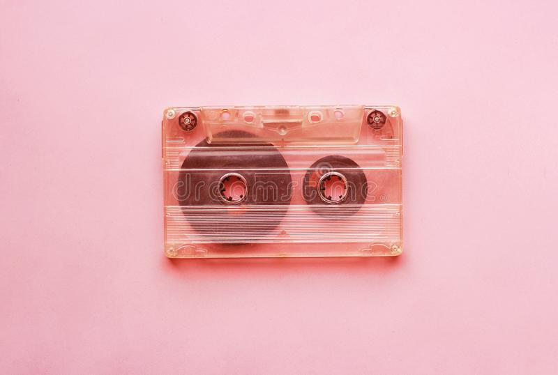 White retro audio cassette, close-up on a pink background, vintage concept stock photo