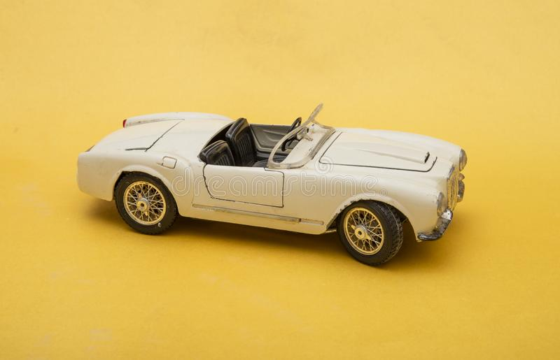 White retro car toy model isolated on yellow background, transportation concept.  stock photography