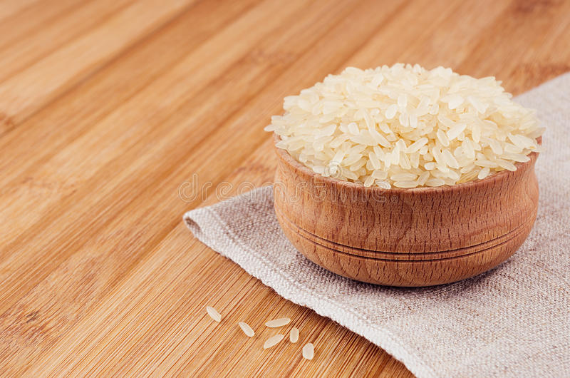 White rice basmati in wooden bowl on brown bamboo board, closeup. Rustic style, healthy dietary cereals background. royalty free stock images