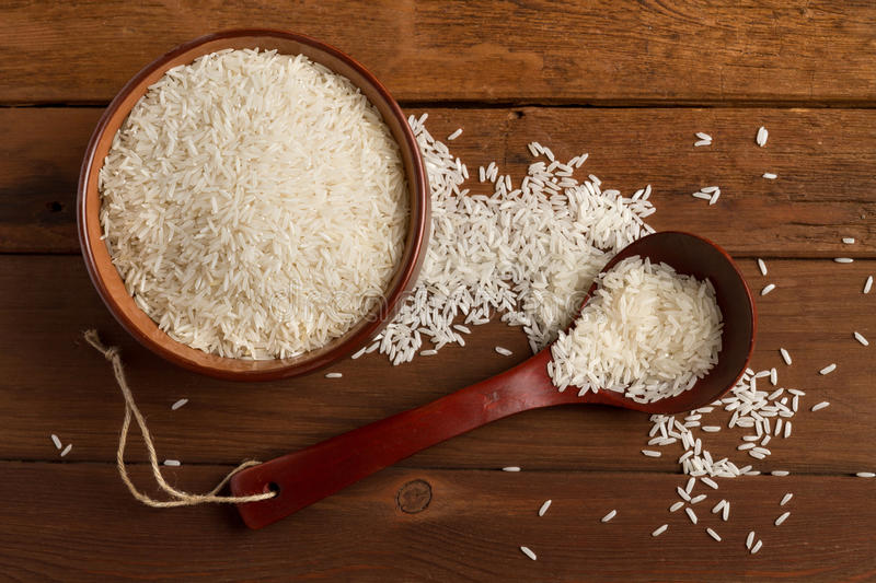 White rice in a ceramic bowl and spoon on a wooden table. (top view stock photography