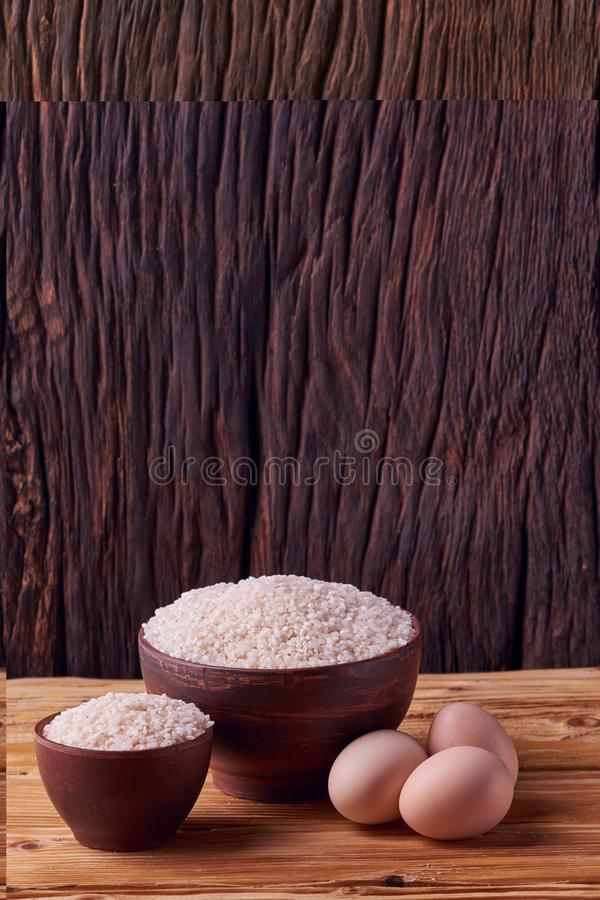 White rice in clay bowl on table and eggs on wood background. Concept asian food stock photo
