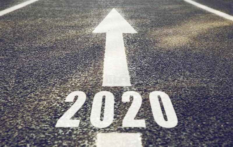 White road marking in form of 2020 year and arrow. Future, new beginning and destination concept - white road marking in form of 2020 year and arrow royalty free stock photography