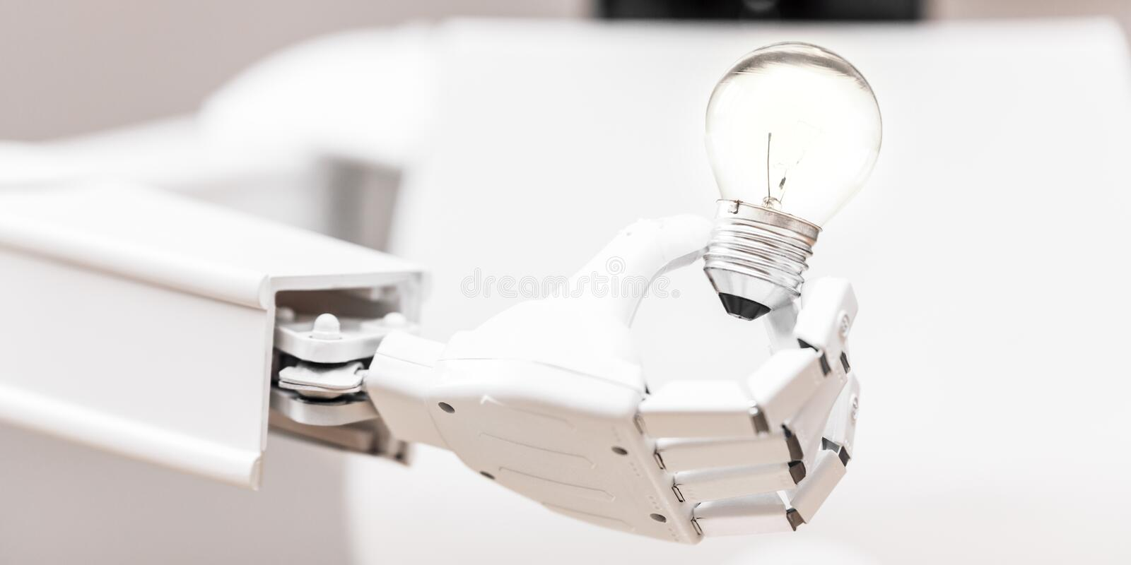 White robot is holding a lightbulb royalty free stock photo