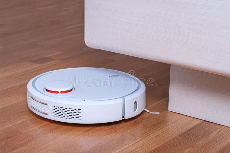 White robot vacuum cleaner runs in bedroom royalty free stock photography