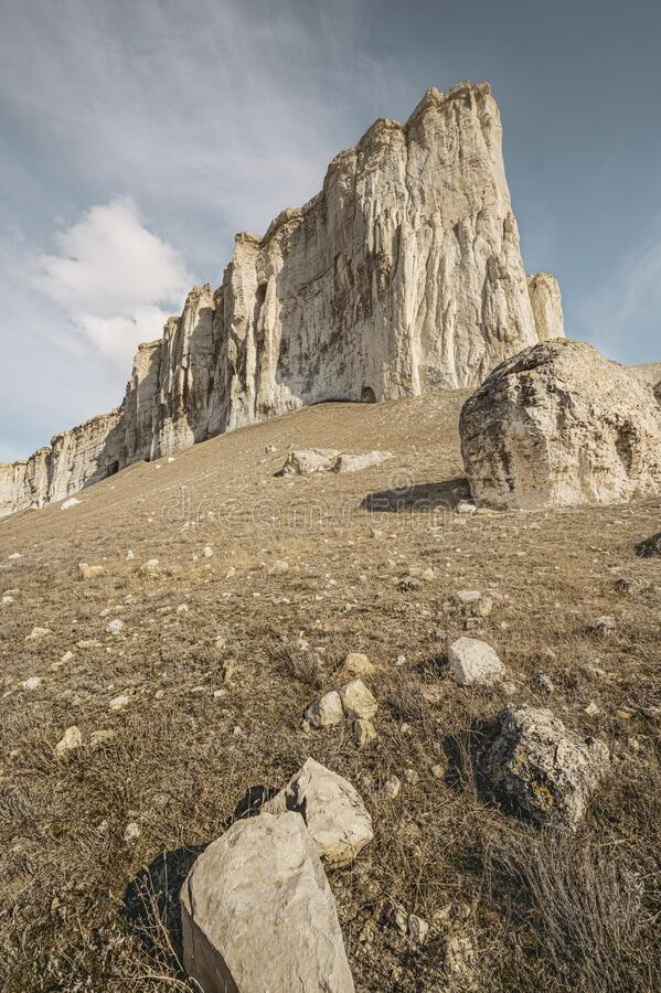 White rock in spring. Mountains. Vertical layout for travel stories. White rock in spring. Mountains. Low angle. Scenic view. Vertical layout for travel stories stock photography