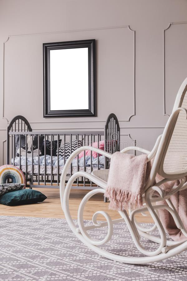White rocking chair with pastel pink blanket in elegant little baby bedroom with grey wooden crib and mockup poster on the wall. Real photo royalty free stock photography