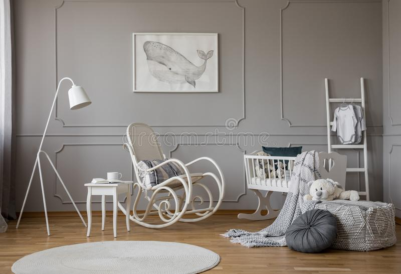 White rocking chair with pillow in the middle of cozy baby room interior with wooden cradle, industrial white lamp and poster in stock photo