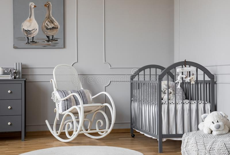 White rocking chair with pillow next to wooden cradle in elegant baby room with duck`s poster on the wall. Concept stock photos