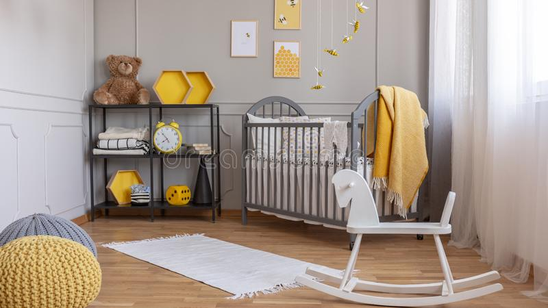 White rocking horse in elegant grey and yellow baby room with industrial shelf and wooden cradle royalty free stock photography