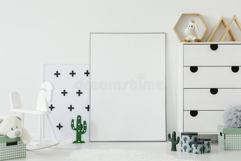 White rocking horse next to empty poster with mockup in kid`s ro stock photo