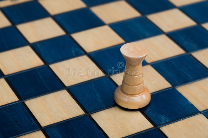 White rook on wooden chessboard. Wooden white blue chess set stock photo
