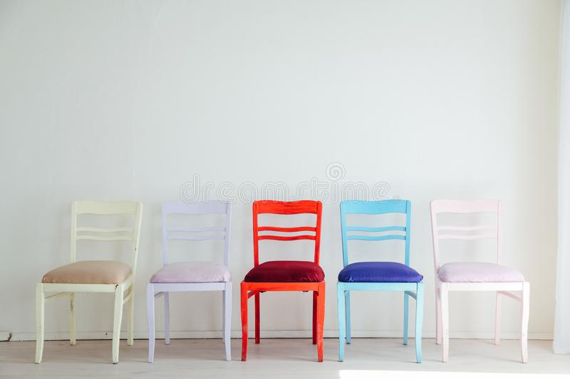 White room with colorful chairs blue yellow red blue purple. Pink royalty free stock photo