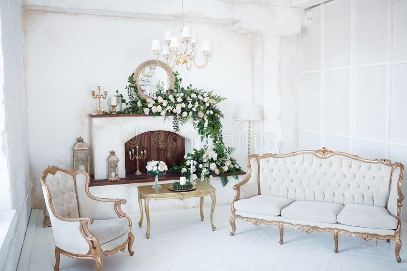 White room with fireplace and carved furniture stock image