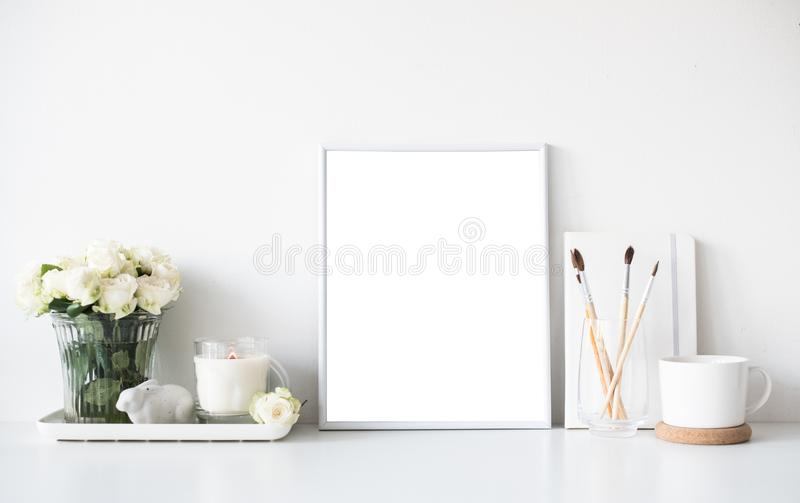 White room interior decor with burning candle, poster mockup and. Bouquet of fresh roses on table, luxury home decorations in daylight closeup royalty free stock photography