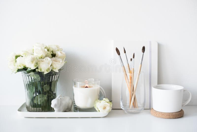 White room interior decor with burning hand-made candle and bouq. Uet of fresh roses on table, luxury home decorations in daylight closeup stock photos