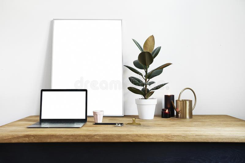White room interior with green plants on rustic wooden table, modern personal laptop, poster in frame with space for layout stock image