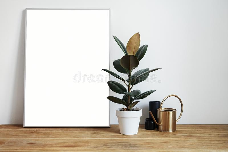 White room interior with green plants on rustic wooden table, modern personal laptop, poster in frame with space for layout.  stock photo