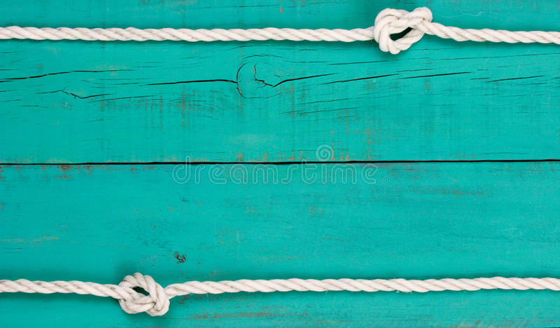 White rope border on blank antique teal blue rustic wooden background royalty free stock photography