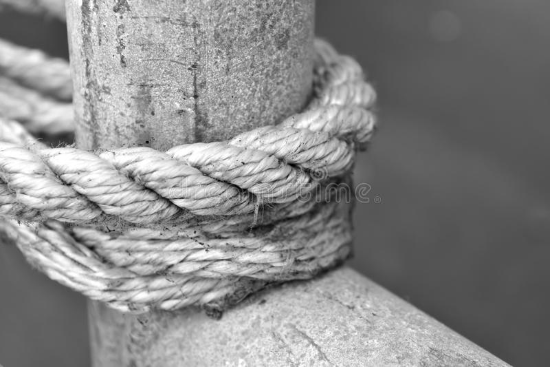 A white rope tied around a wooden pole royalty free stock images