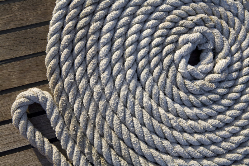 White rope on a wooden surface. White rope rolled up in a circle on a wooden surface stock photos