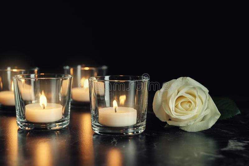 White rose and burning candles on table in darkness royalty free stock photography