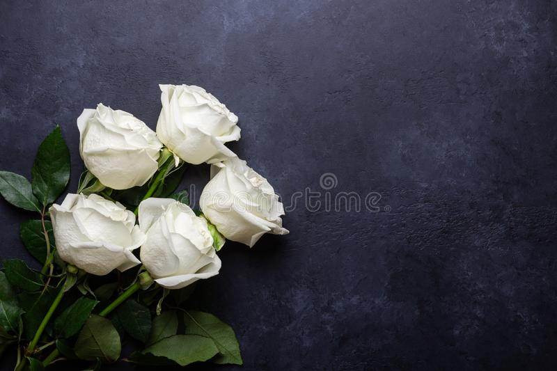 White rose flowers bouquet on black stone background Valentine's day greeting card  stock images