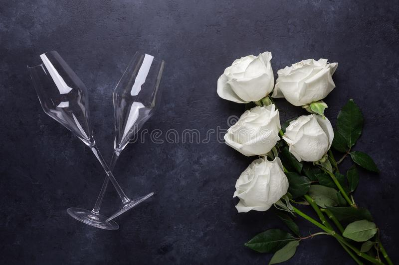 White rose flowers bouquet, champagne glasses on black stone background Romantic greeting card Copy space stock image