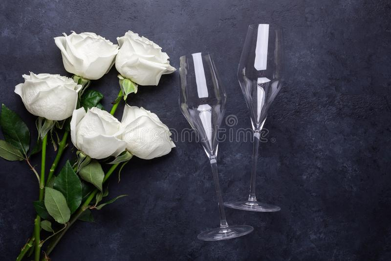 White rose flowers bouquet, champagne glasses on black stone background Romantic greeting card Copy space stock photography