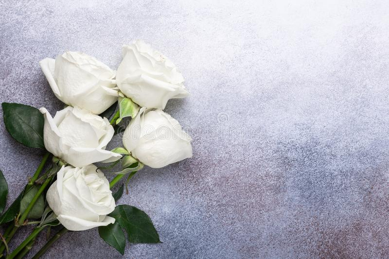 White rose flowers bouquet, champagne glasses on black stone background Romantic greeting card Copy space royalty free stock photography
