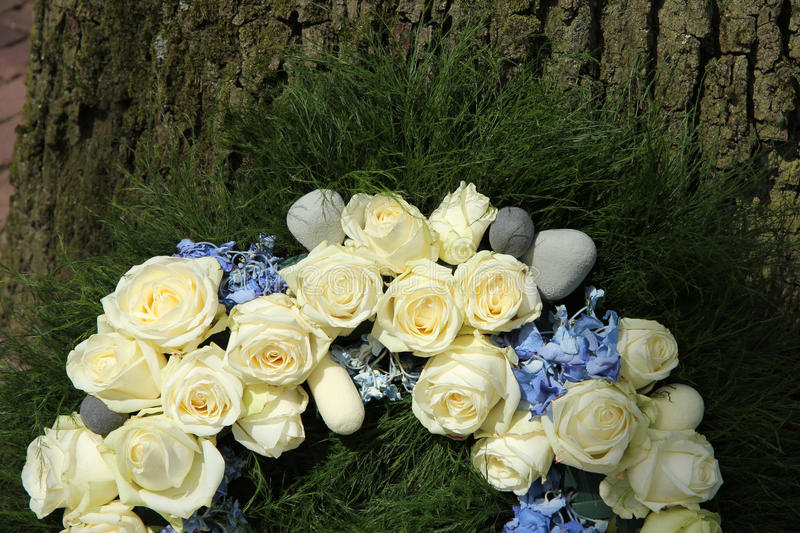 White roses on a sympathy wreath. Detail of a sympathy wreath with white roses and blue hydranghea stock image