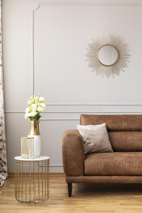 White roses in a vase on the stylish table next to brown leather sofa in light living room. Of elegant house stock images