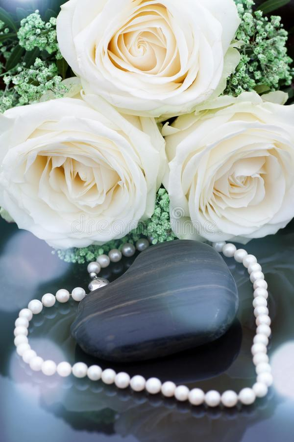 White roses with wedding pearls. Wonderful white roses with festive bokeh and wedding pearls stock photography
