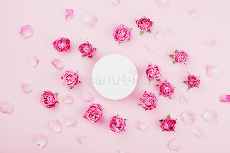 White round blank, pink rose flowers and petals for spa or wedding mockup on pastel background top view. Beautiful floral pattern. stock photography