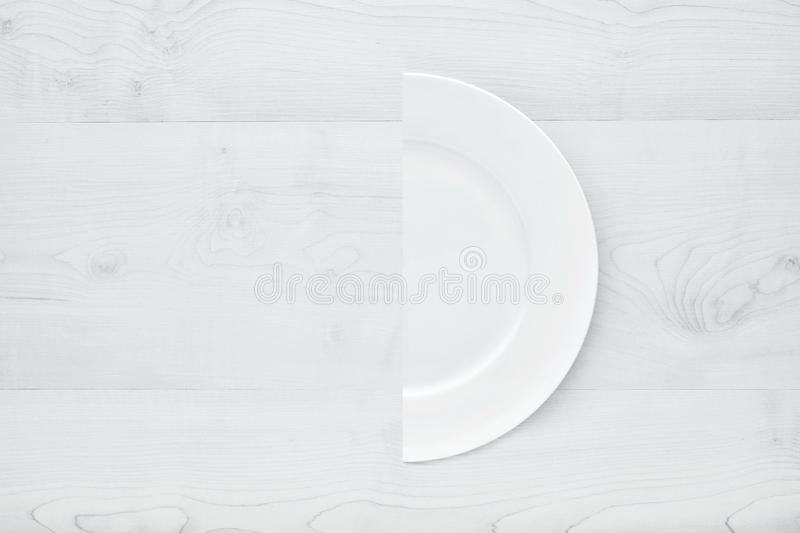 White round ceramic plate cut in half on wooden table. White round ceramic plate cut in half on white wooden table. Concept of diet stock image
