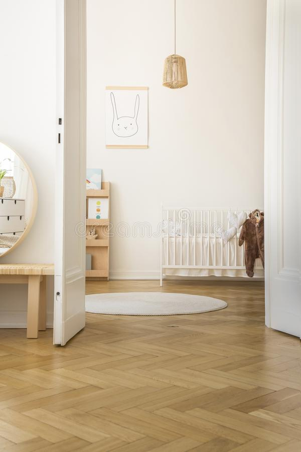 White round rug next to baby`s cradle in bedroom interior with rabbit poster and pillows. Real photo stock images