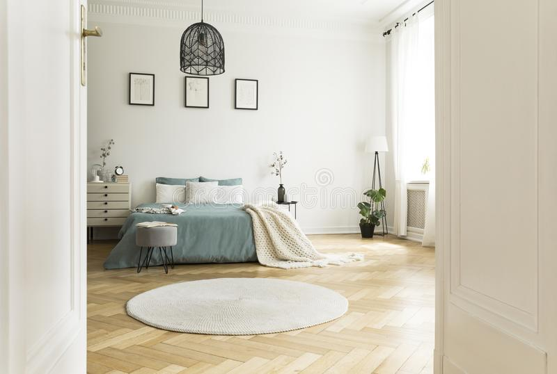 White round rug in spacious bedroom interior with green bed unde. R lamp and posters. Real photo stock image