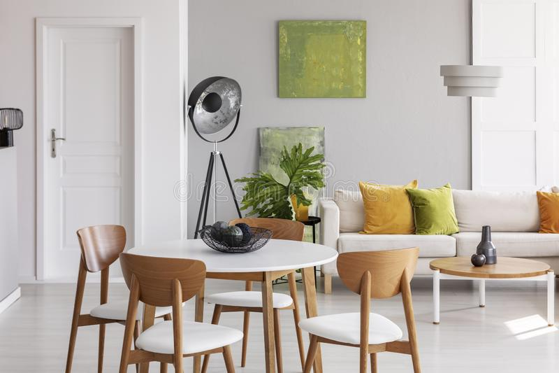 White round table with wooden chairs in the middle of stylish living room with industrial lamp, comfortable couch and golden lime. Accents stock photos