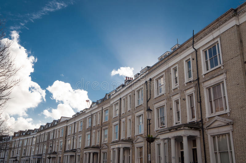 White Row Houses in London, typical architecture. White row houses in London, Earl`s Court, behind the underground station, on a sunny day with clouds. These are royalty free stock images