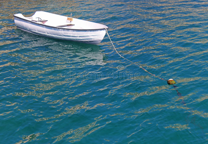White rowing boat anchoring in green water. Little white rowing boat anchoring in blue and green water, sunlight reflections stock photos